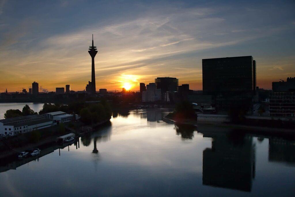 Die Sonne steigt zwischen Fernsehturm und Medienhafen in den Düsseldorfer Himmel.