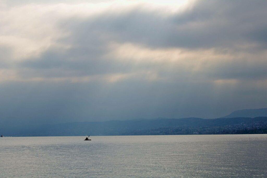 Sonnenstrahlen, Zürichsee und ein einsamer Paddler.
