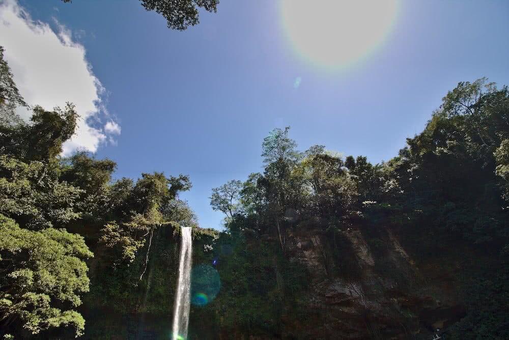 """Über eine grüne Felskuppe stürzt der Wasserfall """"Misol-Ha"""" in die Tiefe."""