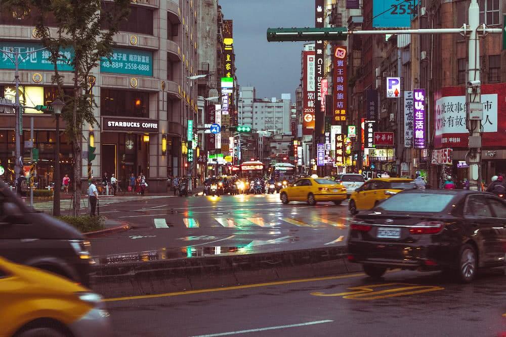 In der Nacht reflektierte die nasse Straße die bunten Farben der Stadt.