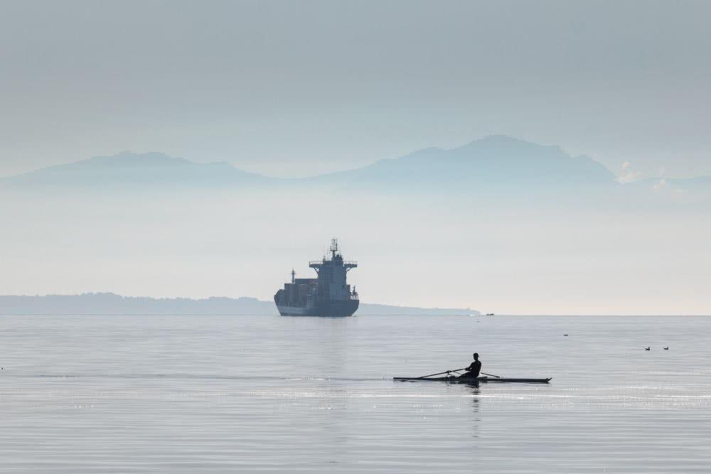 Im Vordergrund das Meer und im Hintergrund entfernte Berge