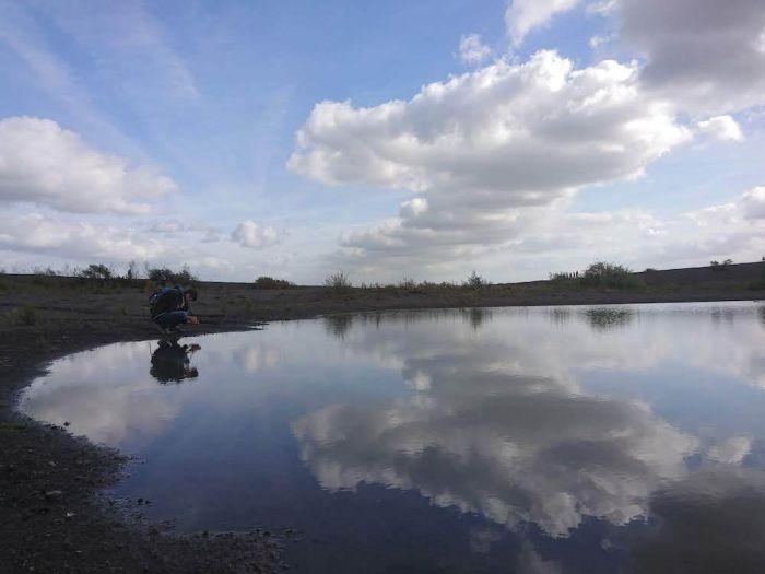 Die Wolken spiegeln im Wasser