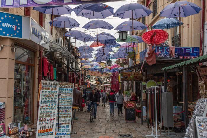 Eine Gasse mit blauen Regenschirmen als Dach in Skopje