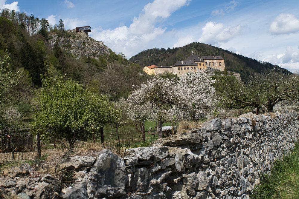 An einer steinigen Mauer entlang bis direkt an der Burg Rabenstein vorbei